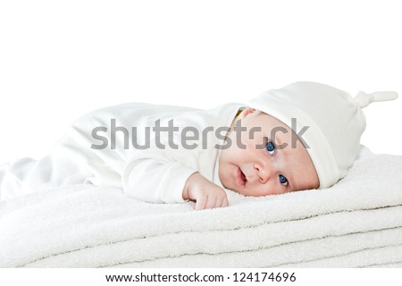 Happy healthy newborn baby boy with blue eyes is lying crawling on a pile of towels and looking at us. Studio isolated on white background. Closeup. Look at my other baby shots in different situations - stock photo