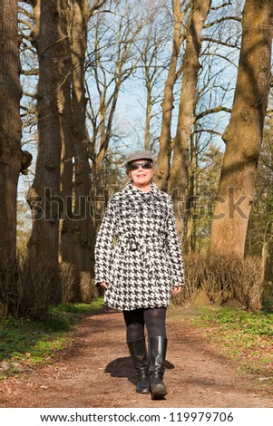 Happy healthy senior woman enjoying nature in forest.