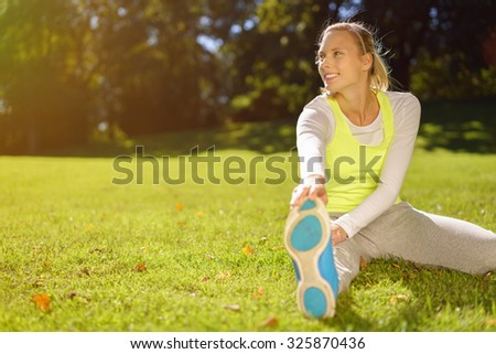 Happy Healthy Young Woman Stretching her Legs at the Park at Early in the Morning. - stock photo