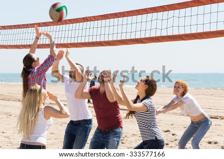 Happy heated friends playing volleyball at sandy beach
