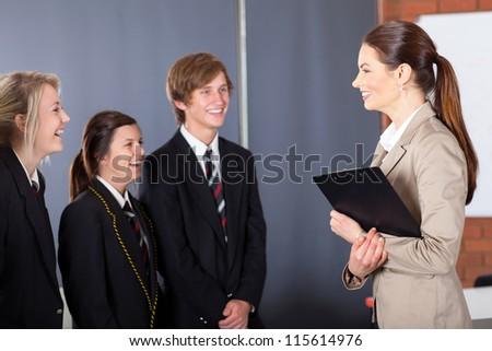 happy high school teacher talking to students in classroom - stock photo