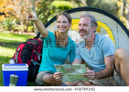 Happy hiker couple holding map and pointing at distance - stock photo