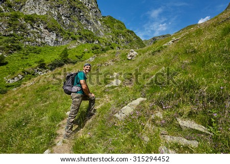 Happy hiker going up to the mountain peak on a very steep trail - stock photo