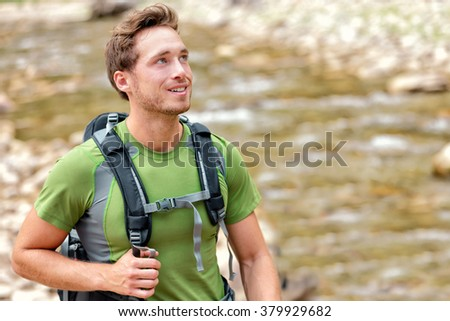 Happy hiker hiking in nature in clean river water. Aspiration young Caucasian man walking in summer nature environment with backpack. Hope, adventure travel or active lifestyle concept. - stock photo
