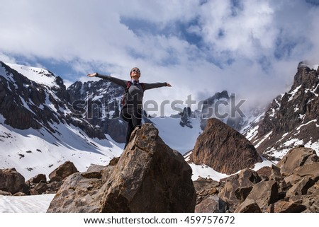 Happy hiker with her arms outstretched, achievement in mountains. Freedom and happiness.