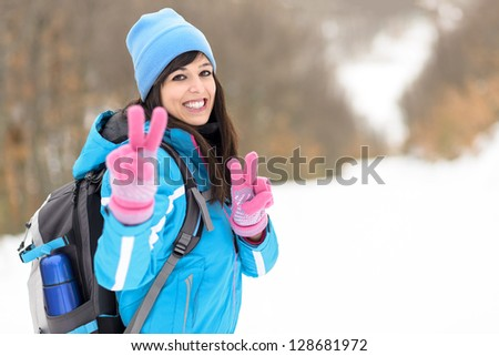 Happy hiker woman walking success with thumbs up on forest. Hiking on winter nature snowy mountains. Caucasian young female model. - stock photo