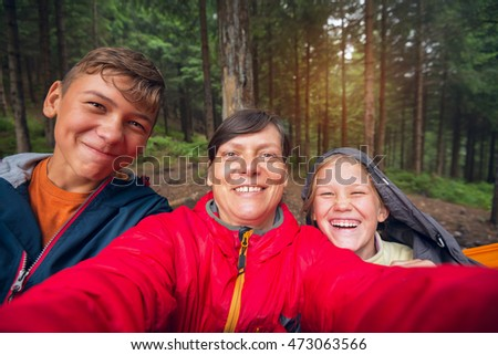 Happy hikers family having fun outdoor and doing selfie. Toned image.