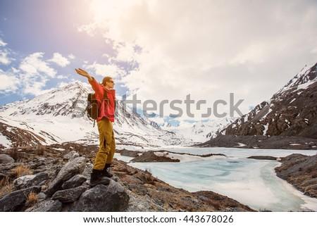 Happy hiking man in high snow mountains near mountain ice lake - stock photo