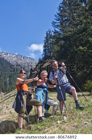 Happy hinking family showing thumbs up sign on a beautiful day in the mountains. - stock photo