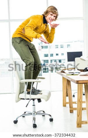 Happy hipster businessman standing on his chair in his office - stock photo