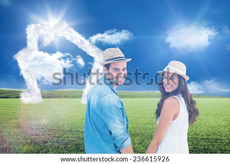 Happy hipster couple holding hands and smiling at camera against sunny green landscape