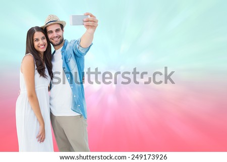 Happy hipster couple taking a selfie against blue and pink light spot design - stock photo