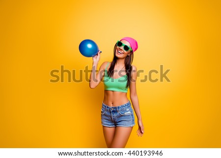 Happy hipster girl in pink hat and jeans shorts inflating balloon on yellow wall
