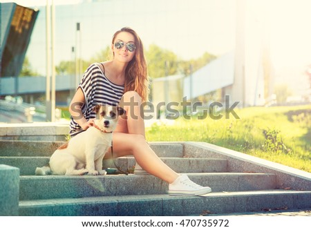 Happy Hipster Girl with her Dog in the City Park. Smiling Woman with Pet Outdoors at Sunset. Toned and Filtered Photo with Lens Flare. Modern Youth Lifestyle Concept.
