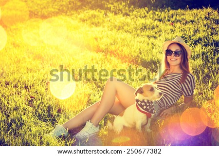 Happy Hipster Girl with her Dog Lying on the Grass. Toned and Filtered Photo. Modern Youth Lifestyle Concept. - stock photo