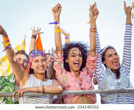 Happy hipsters listening to live music at a music festival - stock photo