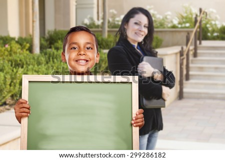 Happy Hispanic Boy Holding Blank Chalk Board on Campus As Teacher Looks on From Behind. - stock photo