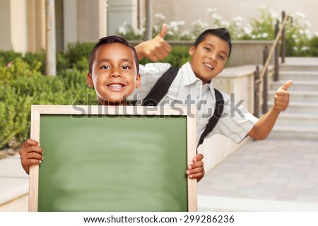 Happy Hispanic Boys with Thumbs Up Holding Blank Chalk Board Outside on School Campus. - stock photo