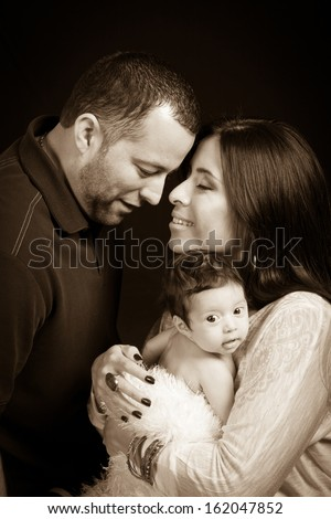 Happy Hispanic Couple adoring their newborn baby girl - stock photo