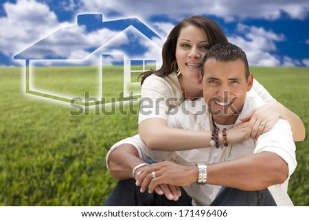 Happy Hispanic Couple Sitting in Grass Field with Ghosted House Figure Behind Them.