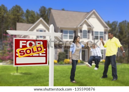 Happy Hispanic Family in Front of Their New House and Sold Home For Sale Real Estate Sign. - stock photo