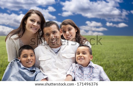Happy Hispanic Family Portrait Sitting in Grass Field. - stock photo