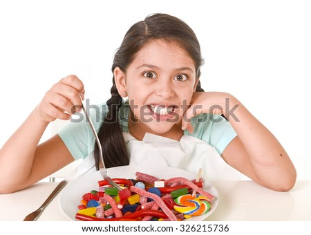 happy hispanic female child eating dish full of candy and gummies with fork and knife  in sugar excess and sweet nutrition abuse isolated on white background