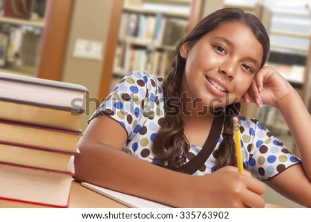 Happy Hispanic Girl Student with Pencil and Books Studying in Library. - stock photo