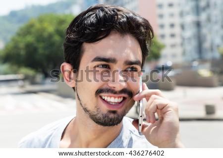 Happy hispanic guy in a grey shirt at phone in city - stock photo