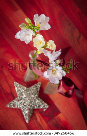 Happy holidays background - Beautiful and fragrant freesias on a blurred backdrop of maroon red  wooden table and silver Christmas star - aerial view with shallow depth of field - stock photo