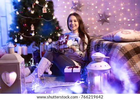 Happy Holidays! Smiling beautiful young woman opening a gift box near Xmas tree at home. Festively decorated interior with garland glowing. Christmas light.