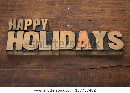 happy holidays  - text in vintage letterpress wood type blocks on a grunge wooden background - stock photo