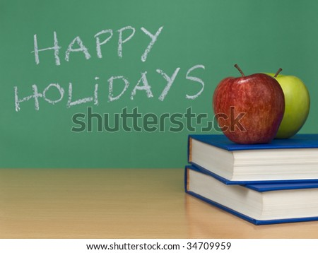 Happy holidays written on a chalkboard. Two apples over books on the foreground.