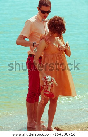 Happy honeymoon concept. Portrait of couple of young happy married hipsters in trendy clothes standing together on the beach. Sunny summer day. Outdoor shot