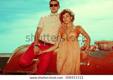 Happy honeymoon (vacation) concept. Young married couple of hipsters in trendy clothes holding hands and posing over old boats background. Sunny summer day. Vintage style. Copy-space. Outdoor shot
