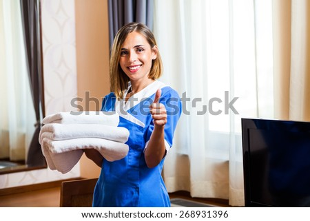 Happy hotel maid holding towels and showing thumb up - stock photo