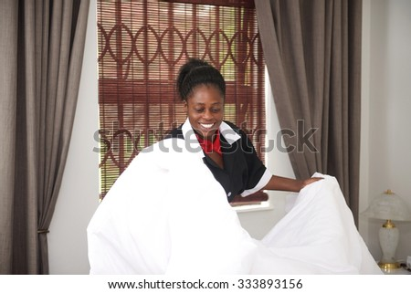 Happy housemaid change bed sheets in room - stock photo