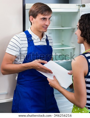 Happy housewife grateful to professional mechanic for help with fridge