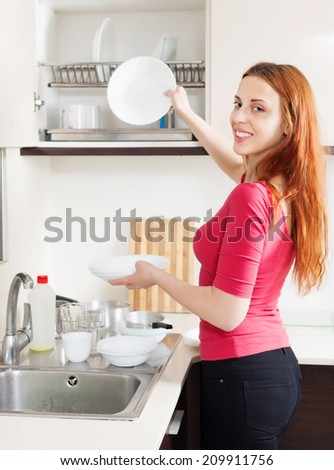 Happy housewife in red washing plates in home kitchen - stock photo