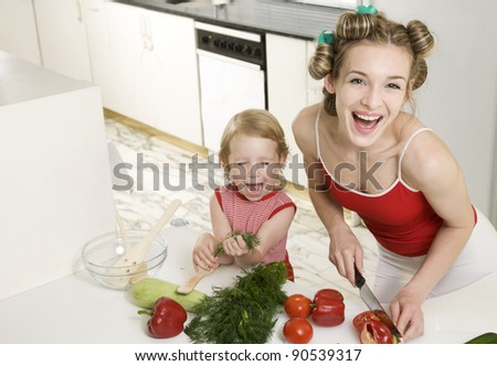 Happy housewife in the kitchen making a salad - stock photo