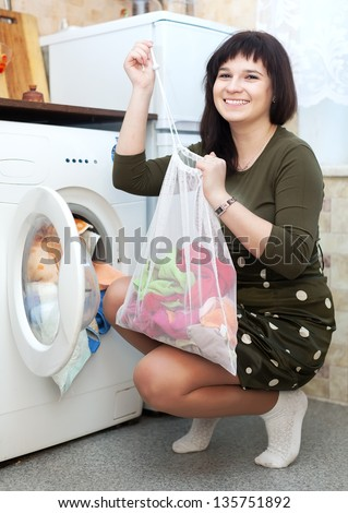 Happy housewife loading the washing machine with laundry bag