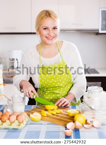 Happy housewife making tasty apple pie at  kitchen - stock photo
