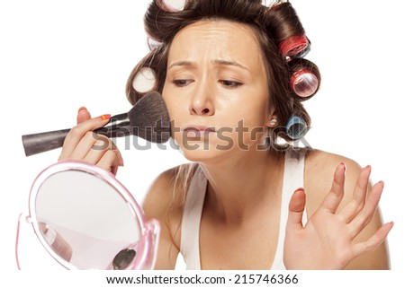happy housewife with curlers to apply makeup on her face - stock photo