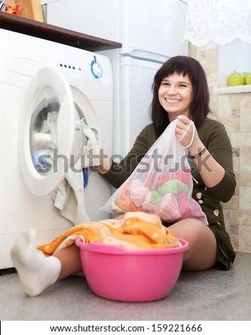 Happy housewife with laundry bag  near washing machine