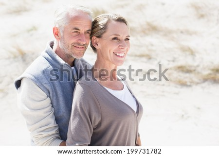 Happy hugging couple on the beach looking away on a bright but cool day - stock photo