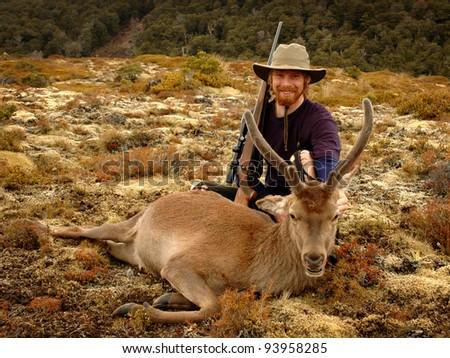 happy hunter with deer - stock photo
