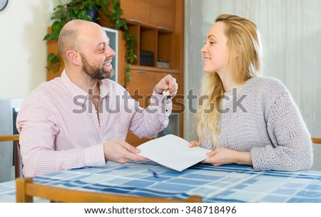 Happy husband and wife signing a contract and buying apartment