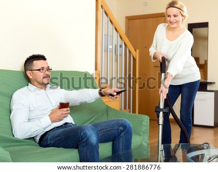 Happy husband is sitting on a couch in a living room relaxing, drinking beer and watching TV while his cheerful wife is vacuuming apartment - stock photo