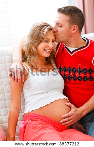 Happy husband kissing pregnant wife and holding her belly - stock photo