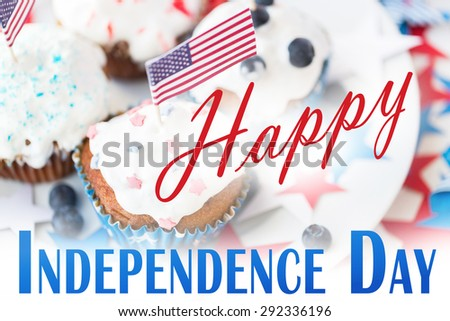 happy independence day, celebration, patriotism and holidays concept - close up of cupcakes or muffins decorated with american flags and blueberries on plate at 4th july party - stock photo